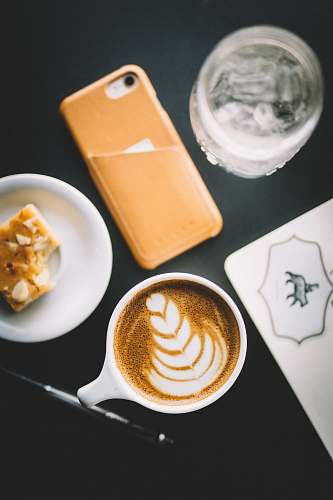cup of coffee selective focus photo of cup of cappuccino beside smartphone, saucer, and glass flat white